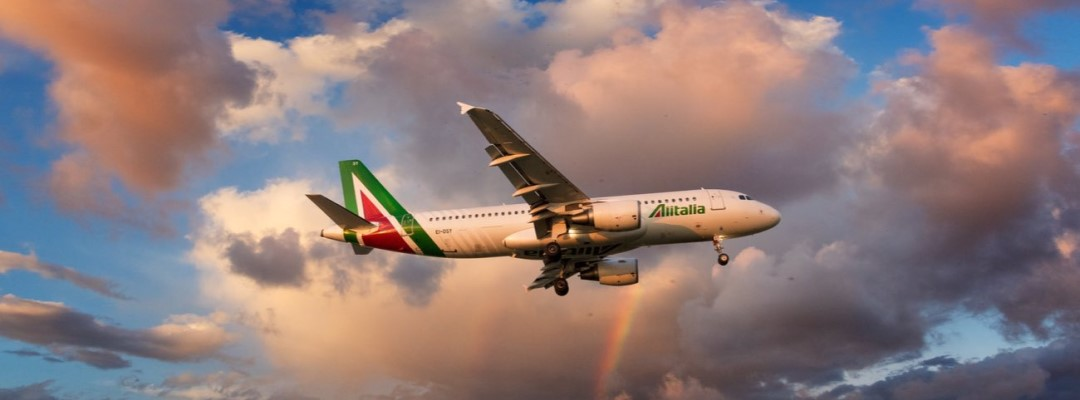 Alitalia Airbus A320 in new livery landing at sunset with rainbow on background