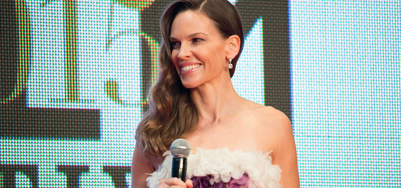 Actress Hilary Swank holding microphone and smiling