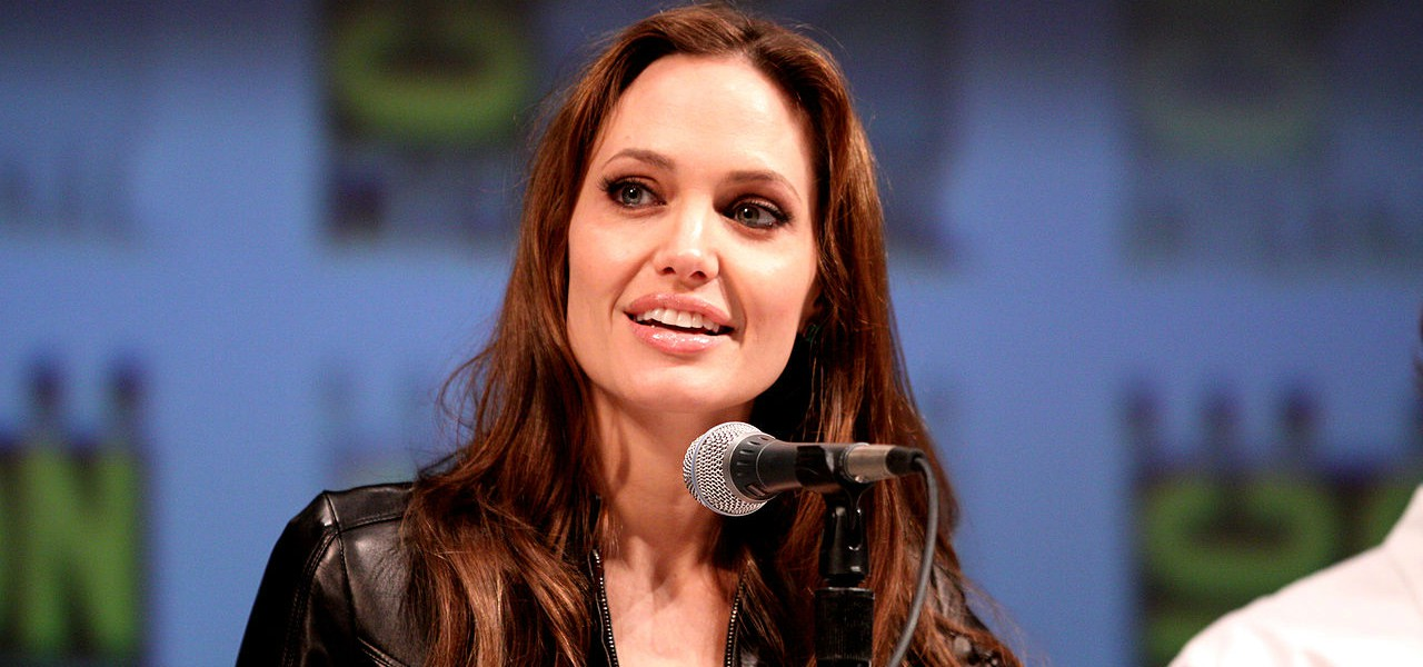 Angelina Jolie smiling at conference with microphone wearing a leather jacket
