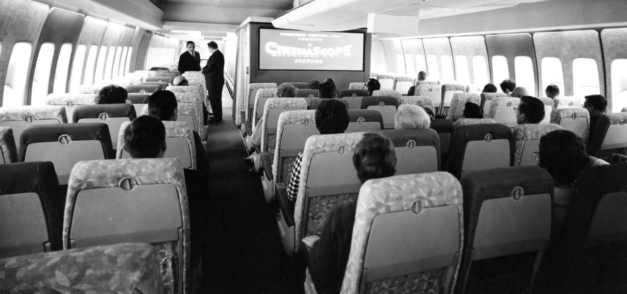 A black-and-white photo of passengers on board a Boeing 747 watching one of the first movies to be shown in-flight