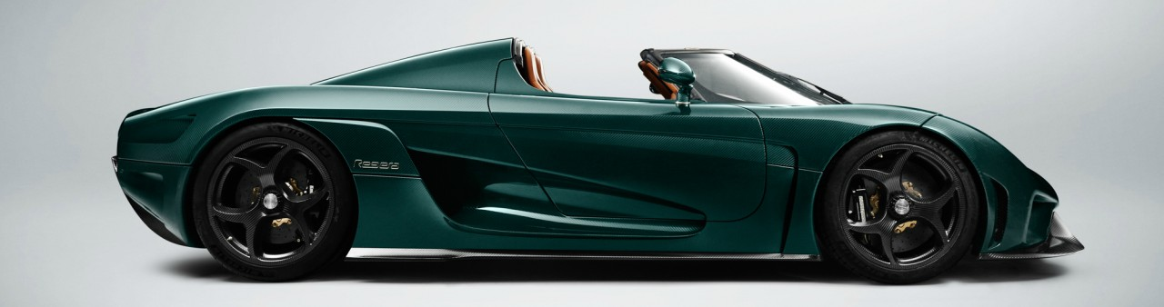 A bottle green Koenigsegg Regera hypercar with its roof down on a plain white background