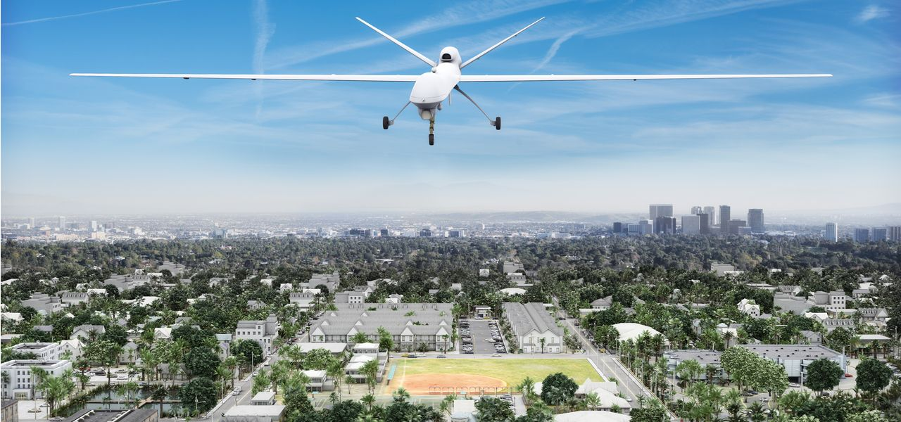 A white unmanned aerial vehicle or UAV flying over a residential urban area on a sunny afternoon