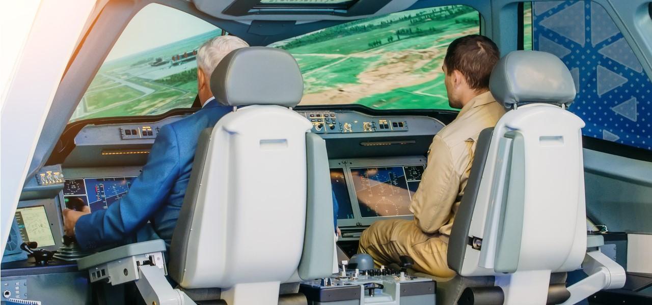 Un piloto y un aprendiz se sientan en la cabina de un simulador de vuelo