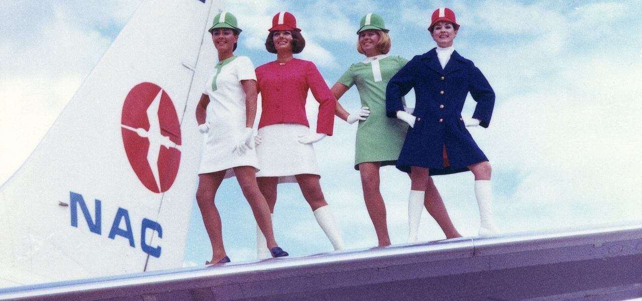 A group of Air Hostesses posing in their 1970s 'lollipop' cabin uniforms on the wing of an NAC plane.