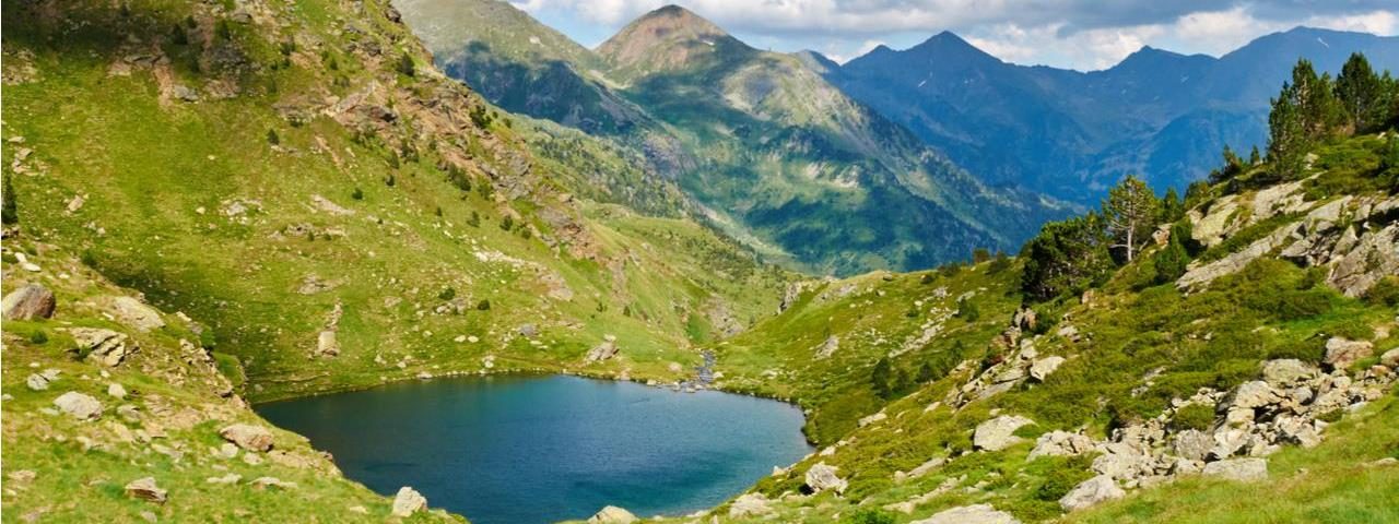 An isolated mountain lake reflecting the blue sky in remote vacation destination Andorra, deep in the Pyrenees
