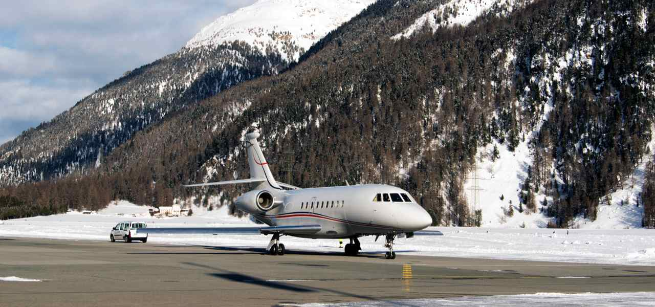 Private jet parked on runway in snow covered mountains