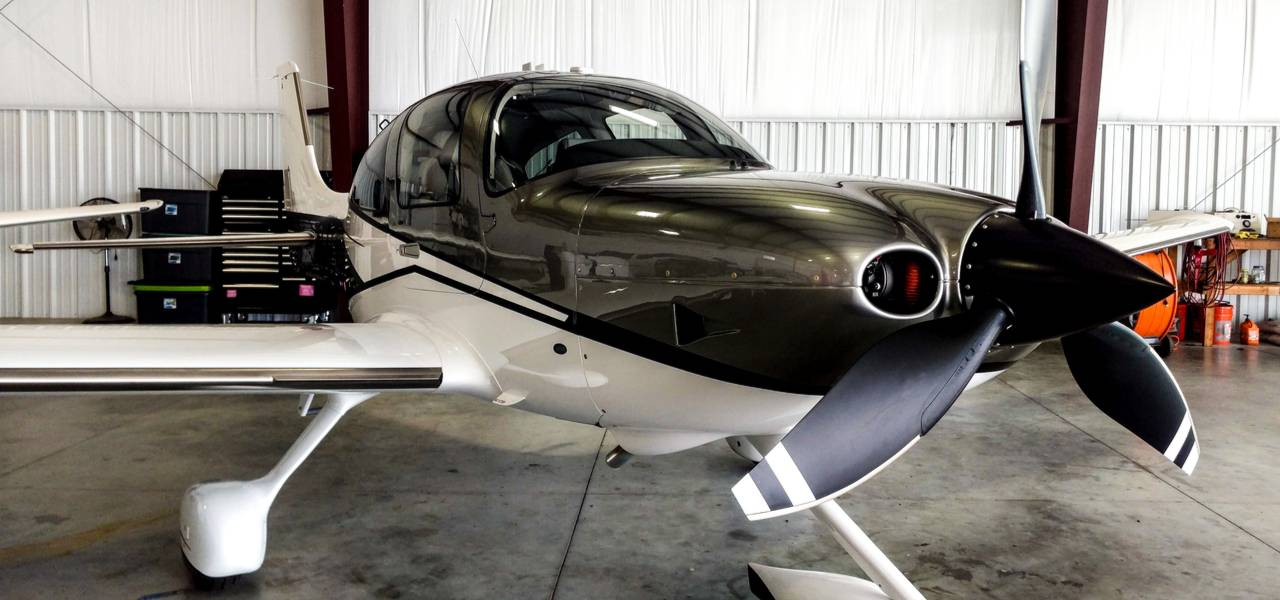 Small single airplane Cirrus SR-22 parked in a hangar