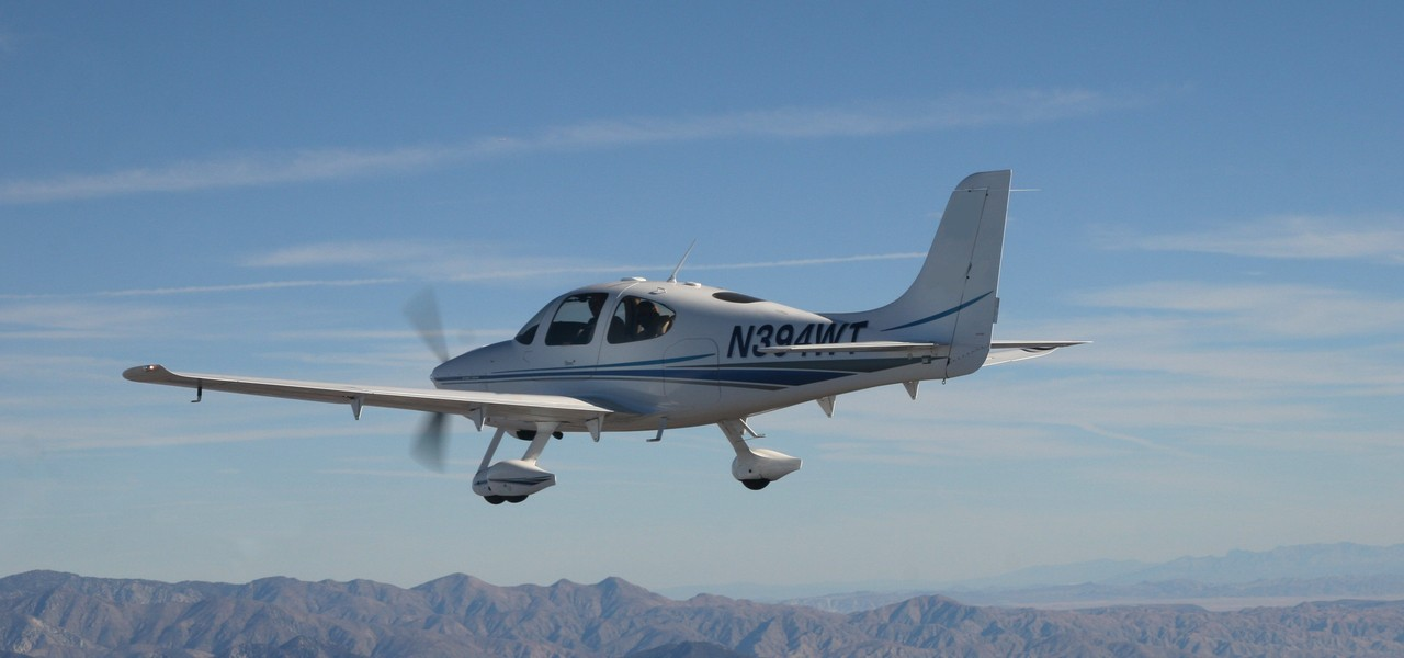 Cirrus SR-22 small private plane flying over mountain range on a sunny day