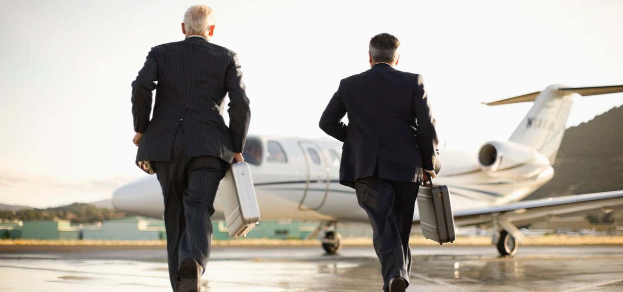 Two businessmen running towards small private business jet