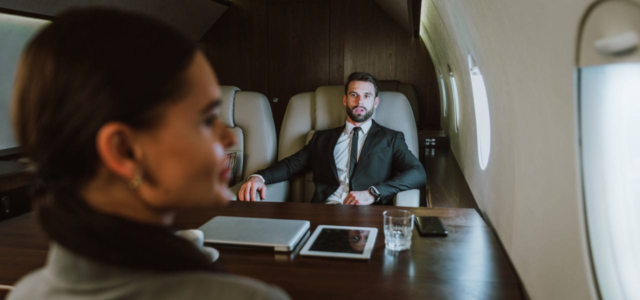 Businessman and woman sitting inside private jet discussing work