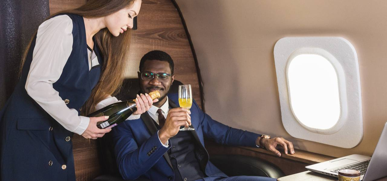 Stewardess aboard private jet offering businessman champagne