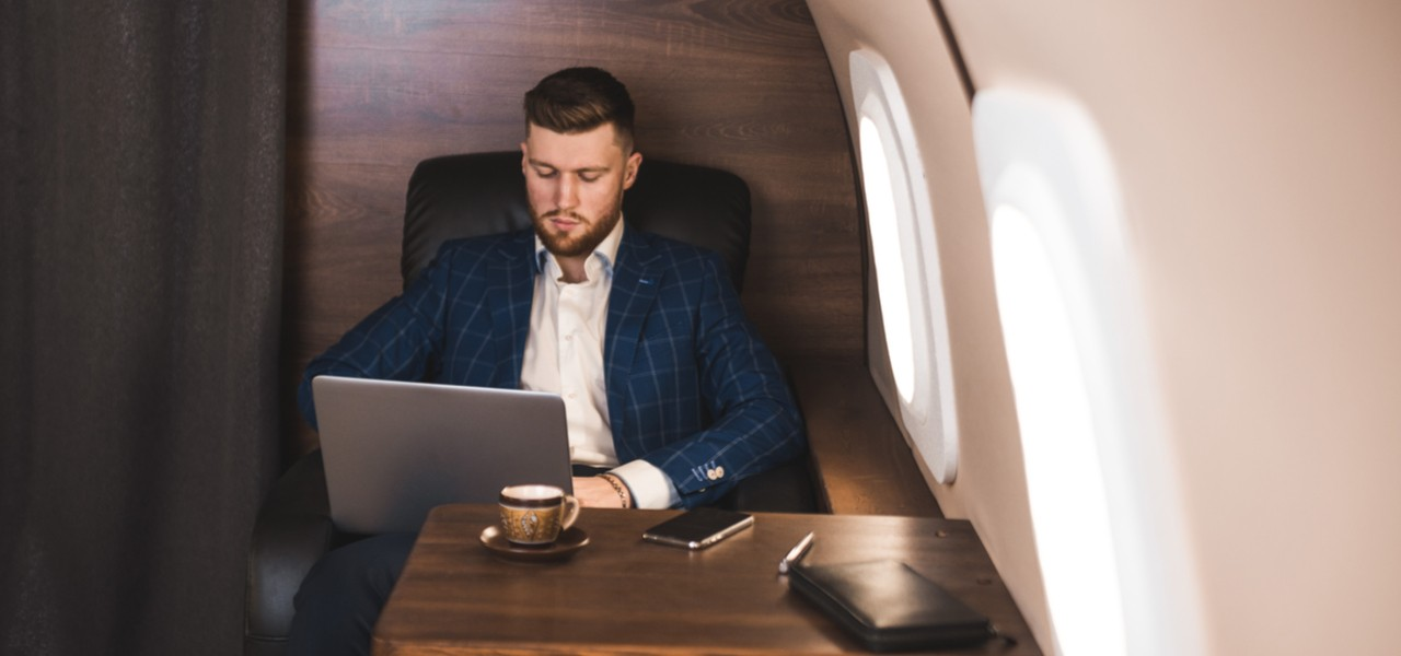 Young businessman working on his laptop on board a private jet