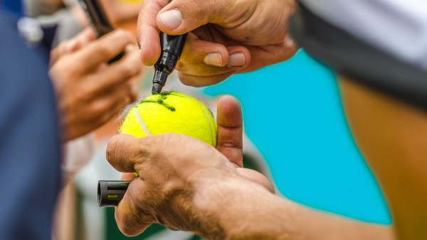 Tennis player signing tennis ball for fans
