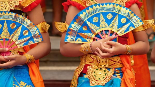 Group of Balinese women in traditional Sarong costumes with fans in hands dancing Legong dance