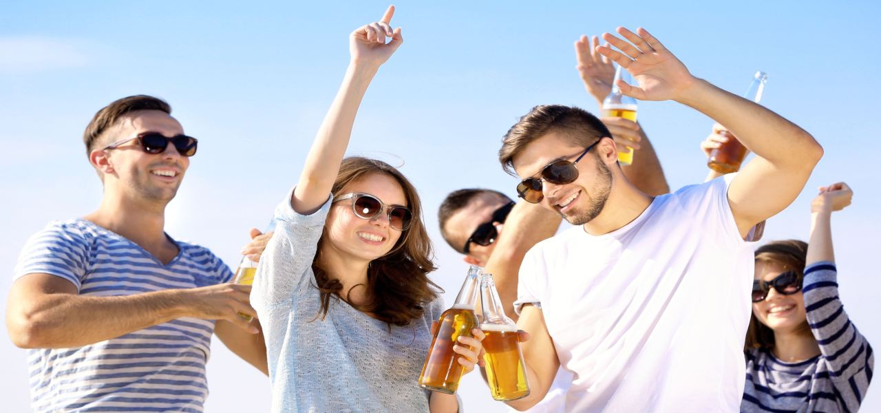 Young people with beer with a blue sky in the background.