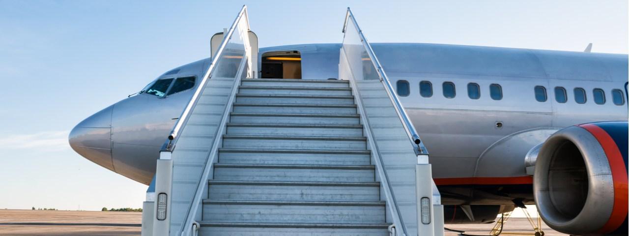 Aeronave de pasajeros con una rampa de abordaje en la pista del aeropuerto.