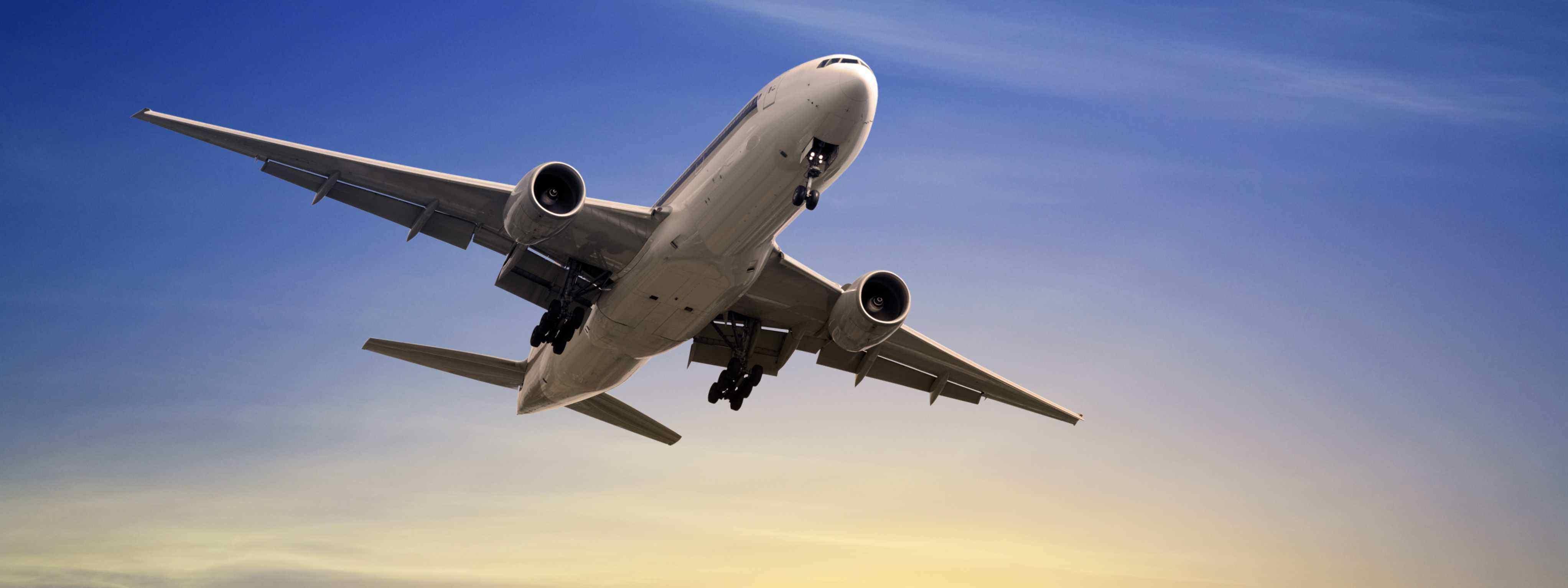Boeing 777 en vuelo con un atardecer de fondo.