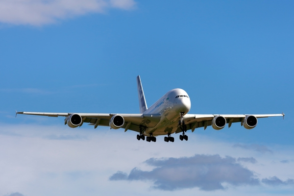 Airbus A380 flying with a blue sky in the background.