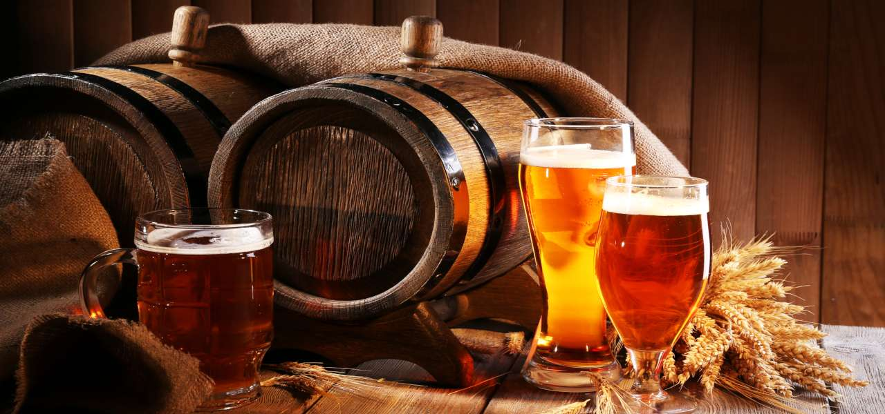 Beer barrel and beer glasses with wheat and hops with a wooden background.