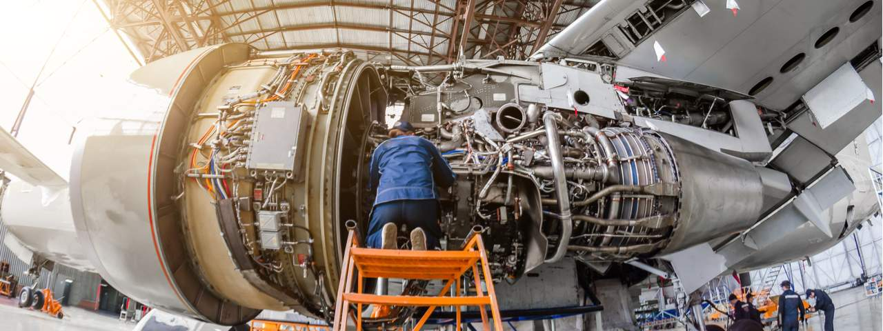 Aircraft mechanic repairs a large airplane engine in a hangar.