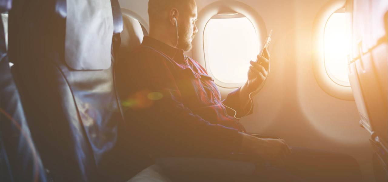 Businessman in an airplane listening to an audiobook on his phone during a flight