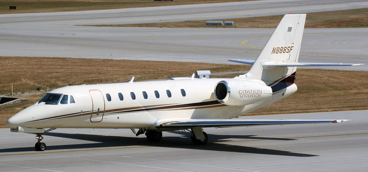 A long shot of a white Cessna Citation Sovereign on a runway