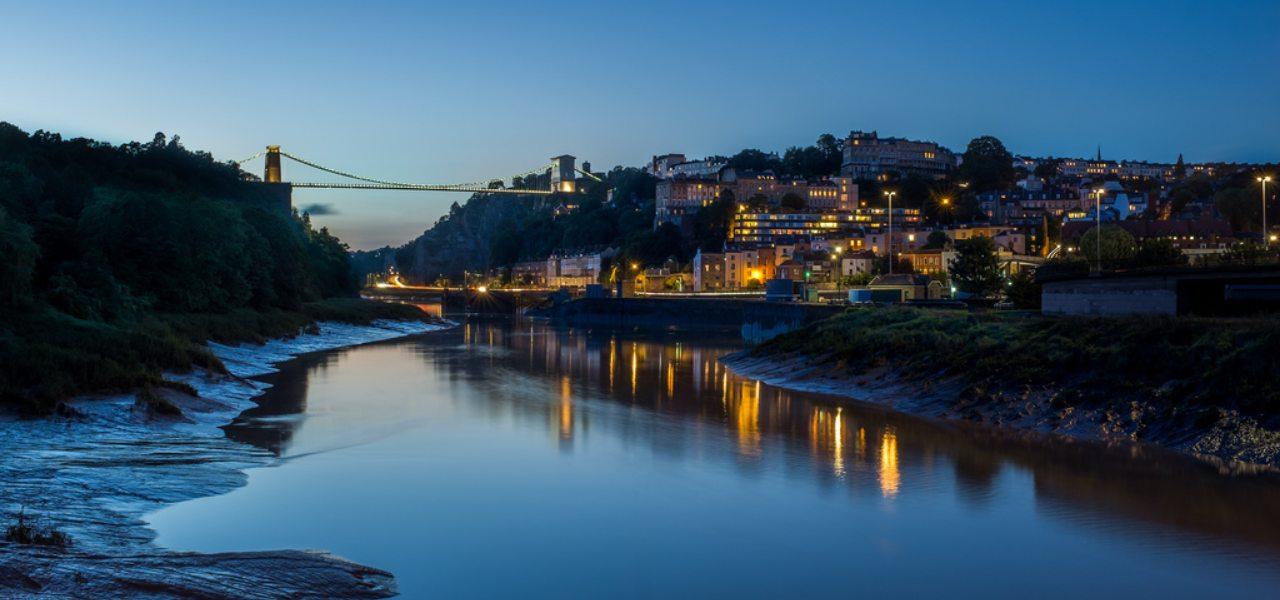 Bristol Harbourside and Clifton Suspension Bridge lit up just after sunset.