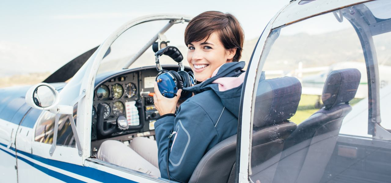 Smiling female pilot in cockpit of small plane