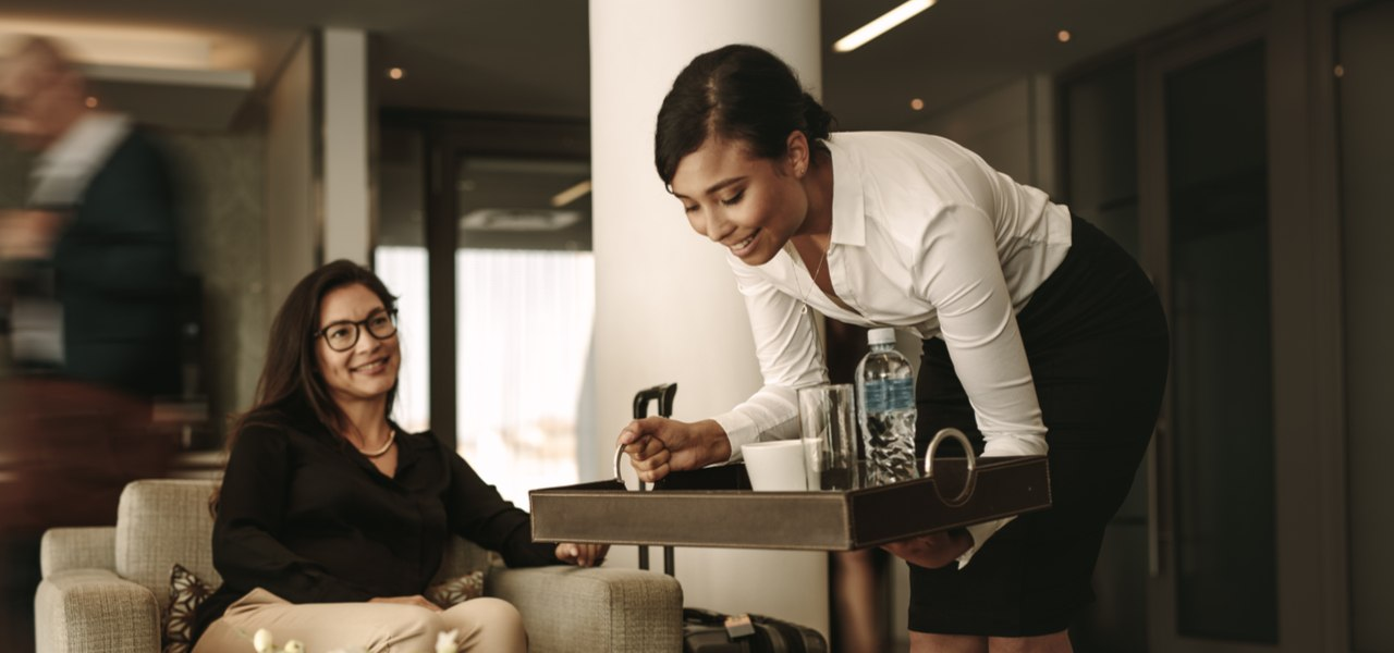 Woman in business class lounge being served drinks by hostess