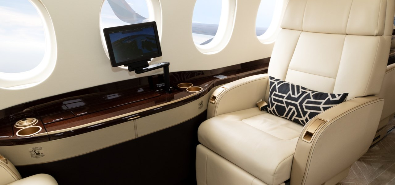 White leather seat interior of business jet with small TV screen