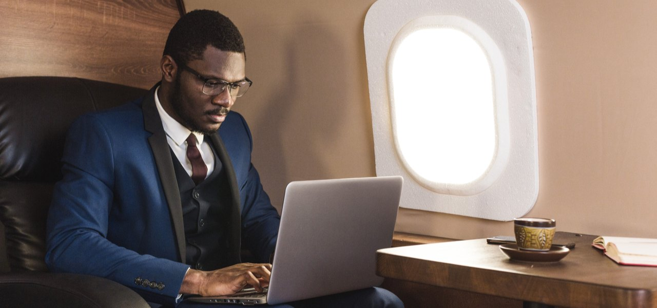 Man working on laptop while sitting in black leather seat on private jet