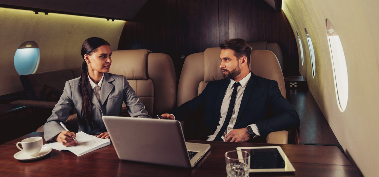 Man and woman doing business in front of a laptop onboard a private jet