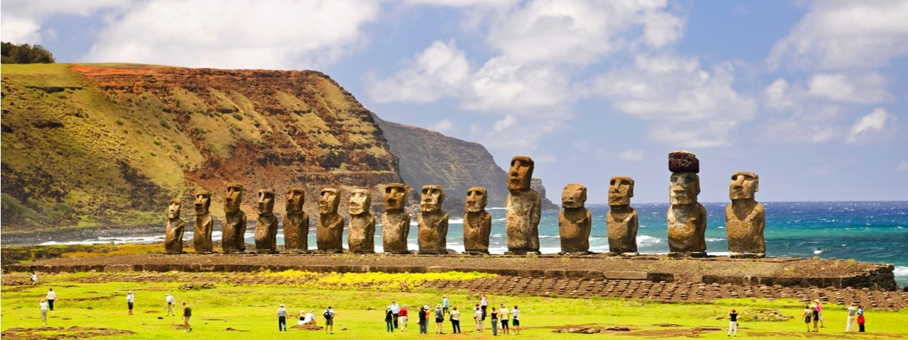 Moais of Ahu Tongariki on Easter Island, Chile, with onlookers in front and the Pacific Ocean behind.