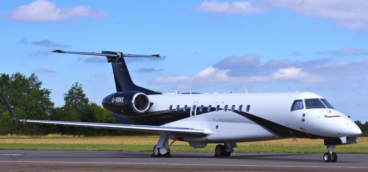 A Blue and White Embraer Legacy 650E on a runway with bright blue skies in the background