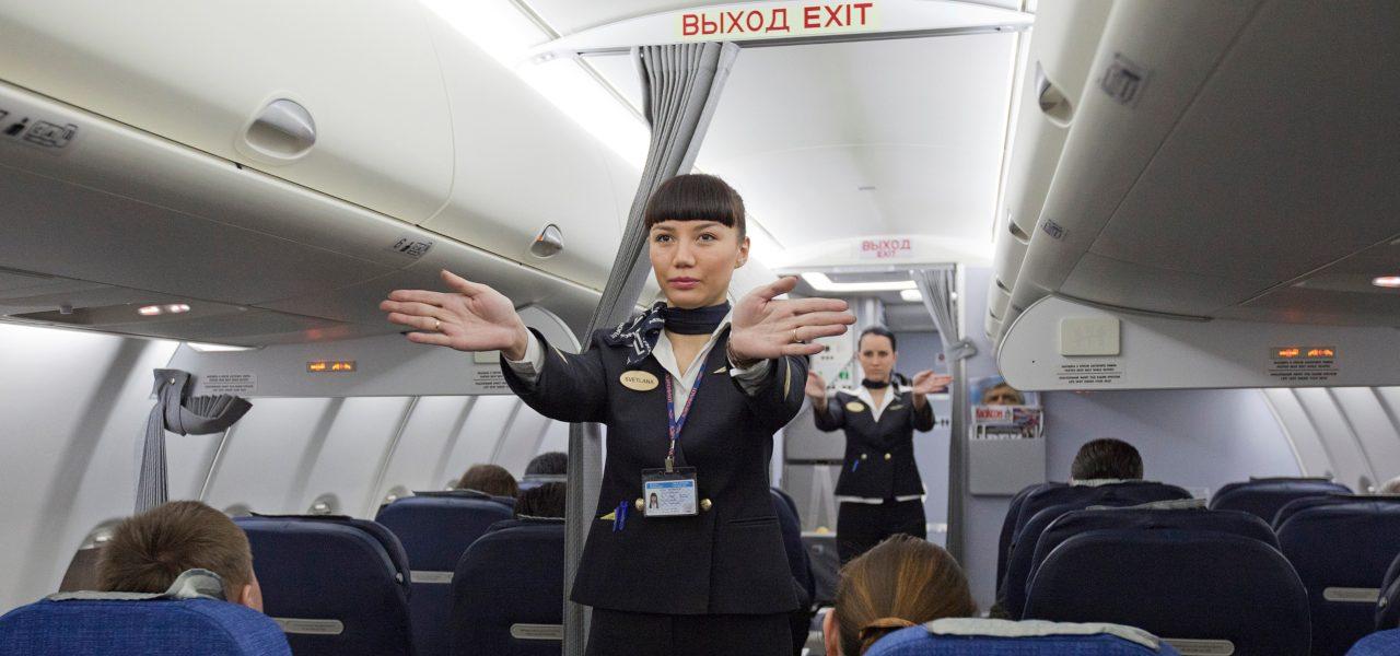 Flight attendants performing a pre-flight safety demonstration