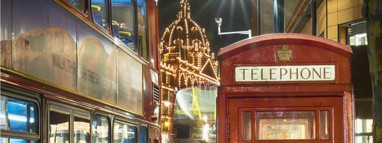 Harrods department store lit up at night behind a red London telephone box