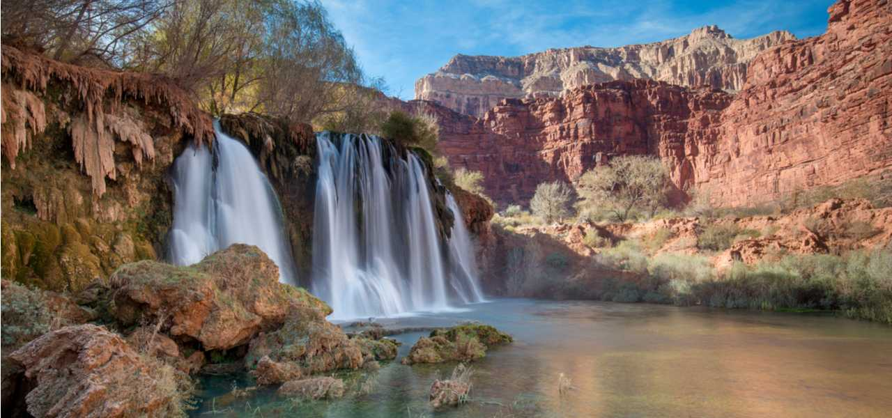 Havasu Falls Hike located in Arizona, with waterfalls on a blue sky day.