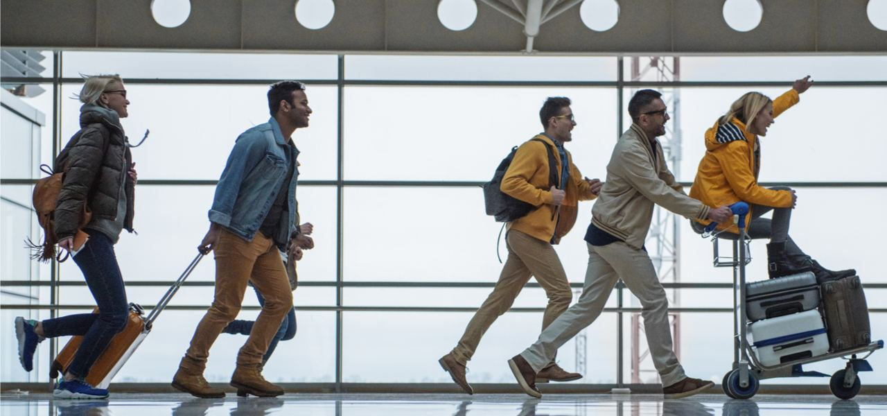 Group of friends in airport walking and one riding on a luggage trolley