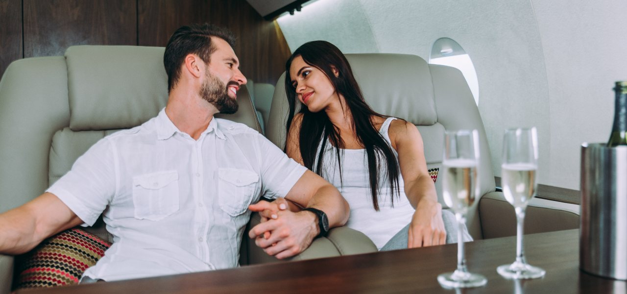 A young couple drinking champagne on board a private jet