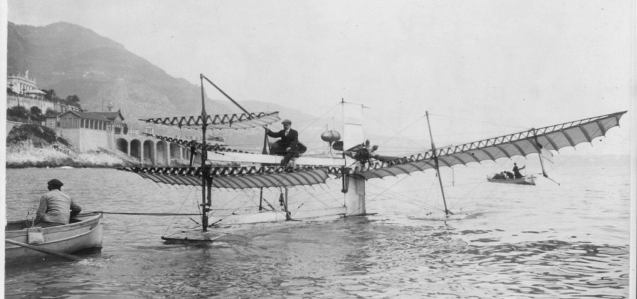 Henri Fabre sat on his seaplane whilst man in rowing boat helps pull the plane to the shore.