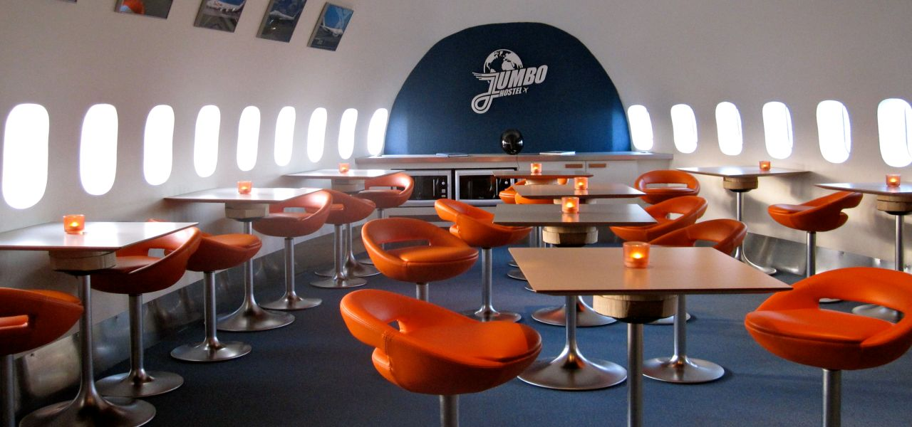 Orange chairs and tables inside the Stockholm Jumbo Hostel