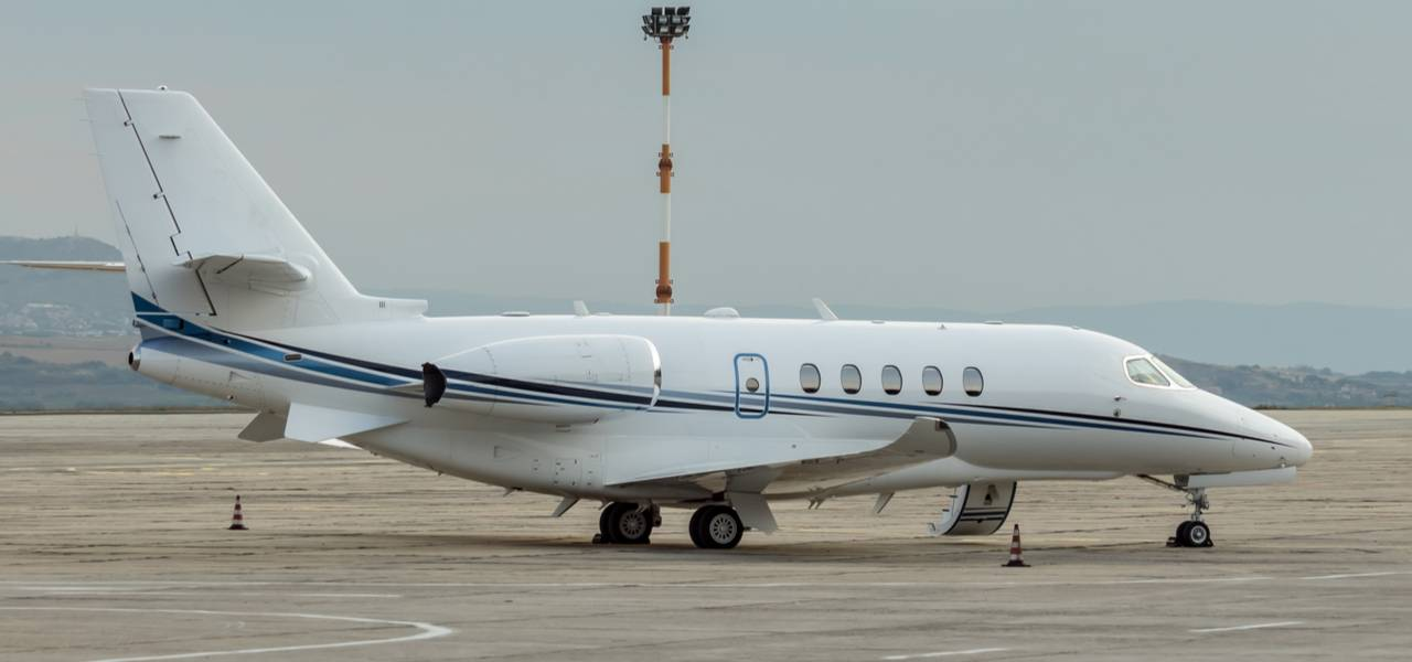 White Cessna Citation on tarmac at a side angle
