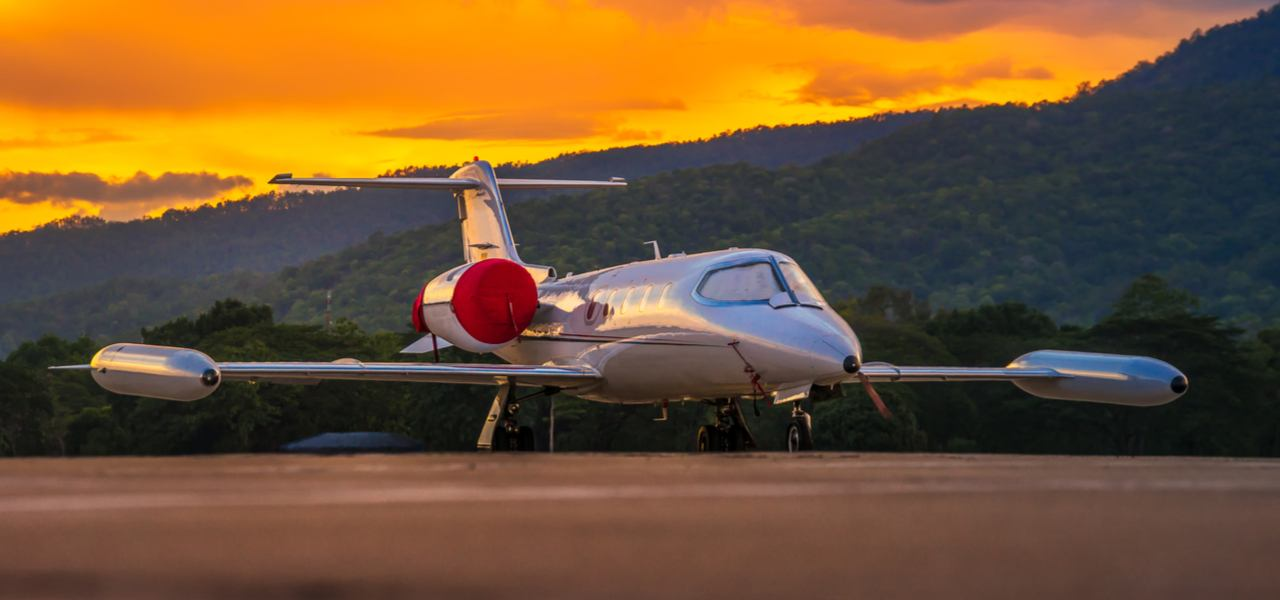 Bombardier Learjet parked on tarmac with beautiful sunset in background