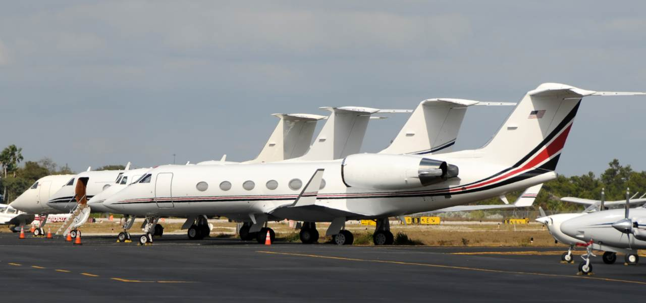 Row of midsize luxury private jets on tarmac