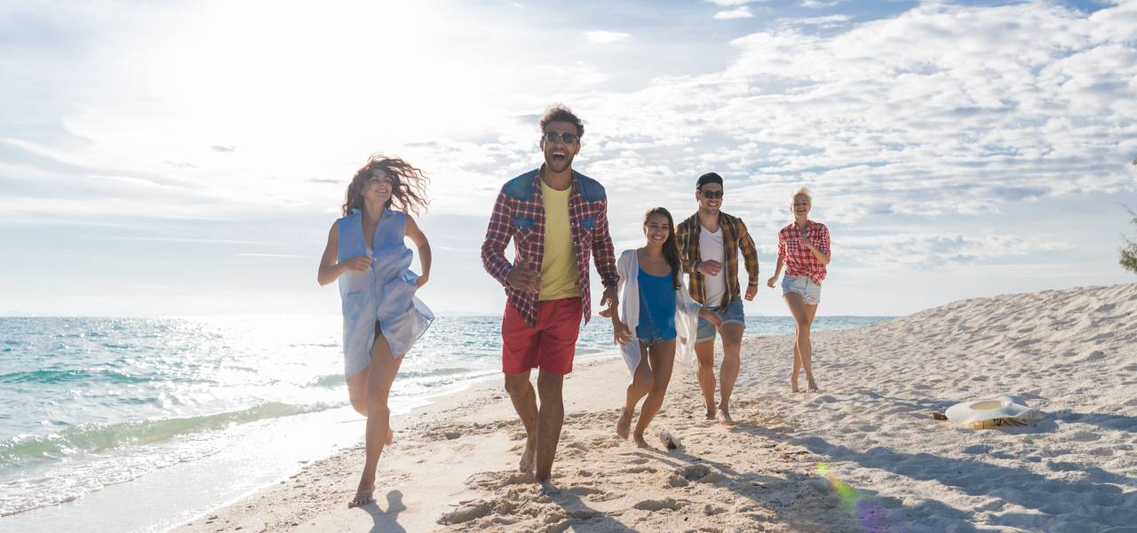 Group of friends running and laughing on a beach
