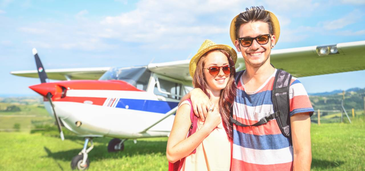 Young couple stand smiling on a sunny day in front of a small private plane
