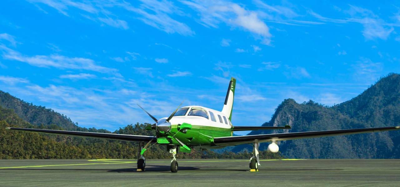 Green and white small private jet on runway on a sunny day with mountains