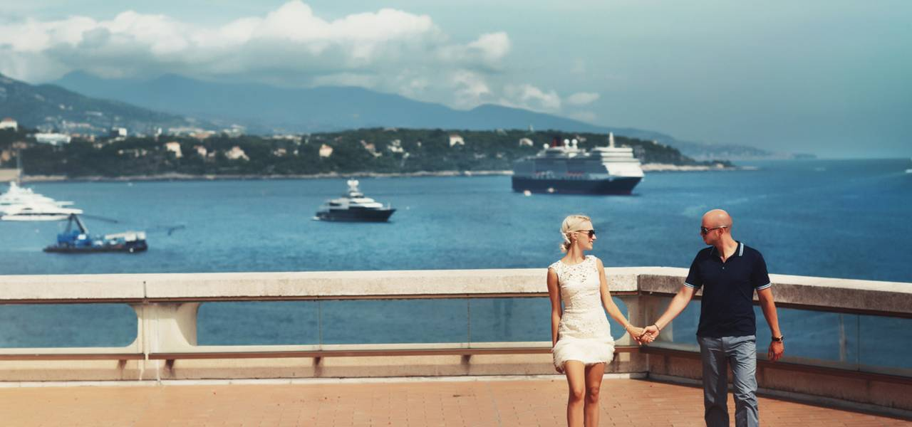 Young couple in love on holiday in Monaco with yachts on water behind them