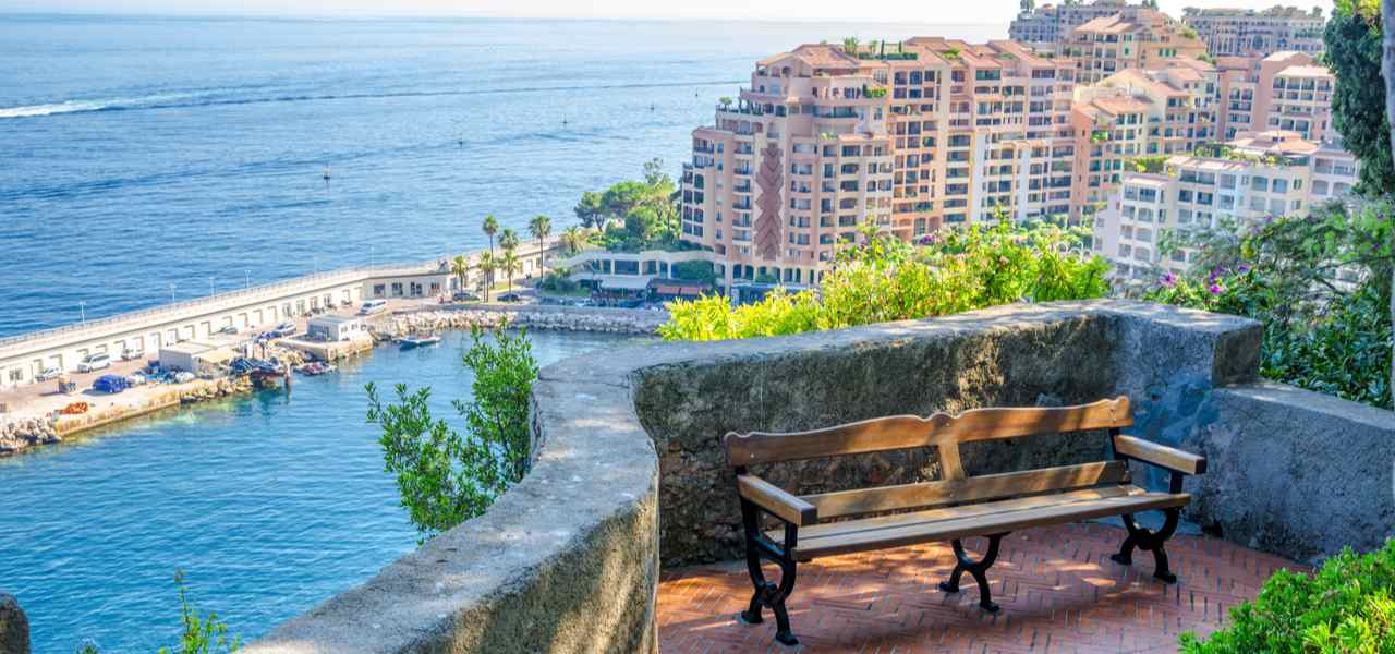 View of Monaco harbour from mountain with bench in foreground
