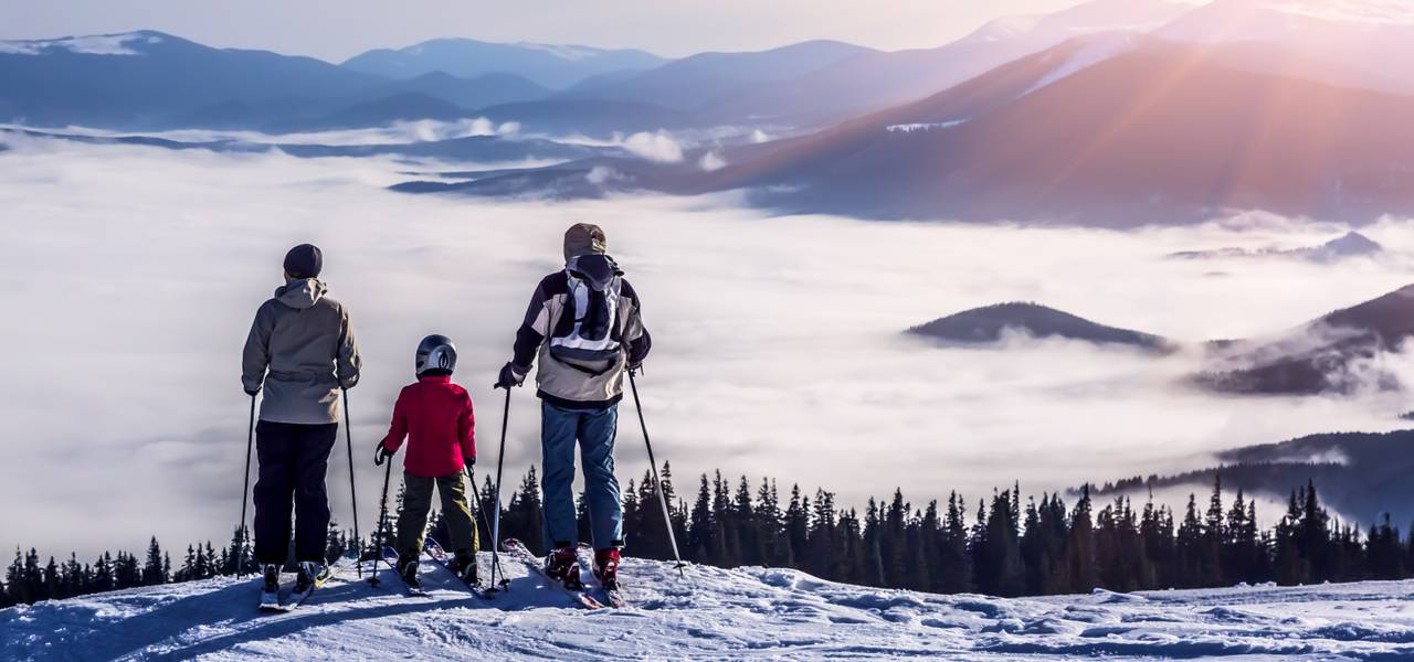 Family with young child looking out at snow and mist at ski resort